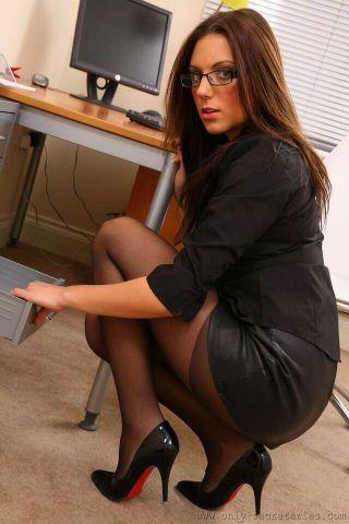 Mulher morena, com longos cabelos castanhos claros, está agachada , Usa uma saia de couro preto justa ,onde se vê a meia preta , além de uma camisa preta muito fina. Ela olha olhando assustada.