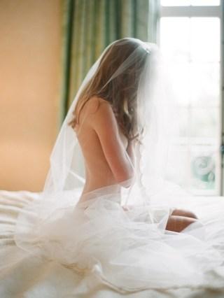 Moça sem roupa apenas com o véu de noiva sentada nua sobre a cama. O rosto está escondido e pela janela do quarto entra uma luminosidade que infere que está no início da manhã. O cenário é de intimidade e paz.