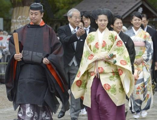 Princesa Noriko do Japão, e seu noivo, caminham um ao lado do outro, usando trajes típicos de um casamento shintoista, logo atrás um cortejo de inúmeras casais, os homens vestem fraque e as mulheres vestem trajes típicos japoneses.