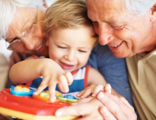 A imagem mostra um avô e uma avó de cabelos brancos, como rostos colados em um menino de 1 ano loiro com olhos azuis mexendo em um brinquedo de plástico. Mostra bem a ternura entre avós e netos