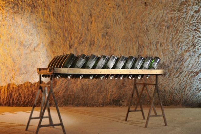 Imagem de um adega sub-terrânea , que eram túneis construídos pelos romanos, onde temos várias garrafas apoiadas de ponta cabeça, numa mesa de descanso , com pouca iluminação e temperatura controlada.