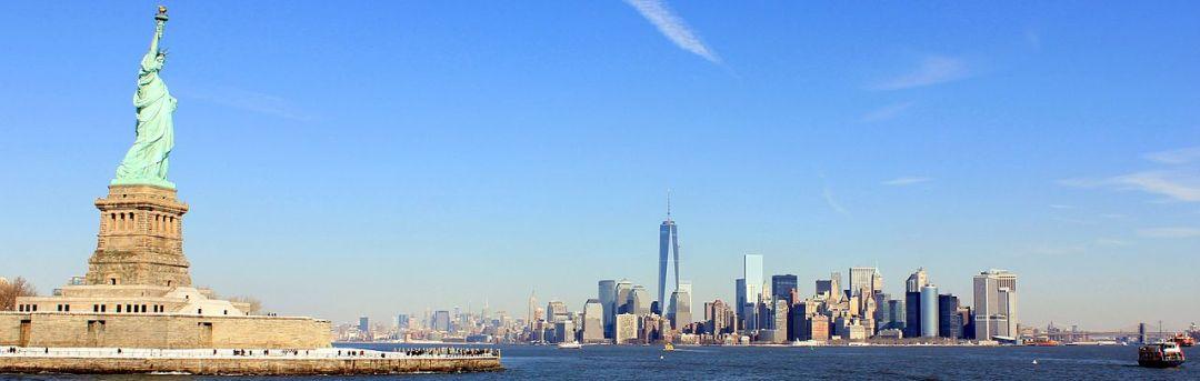 foto da cidade de Nova Yorque, em visão lateral, onde temos no primeiro plano a esquerda a estátua da liberdade e ao fundo a belíssima cidade , num dia belíssimo céu azul.