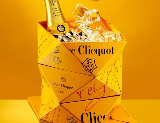 Num fundo todo amarelo ouro, temos um Balde de gelo, em forma de dobradura triangular, na cor amarelo ouro, classico da Champanhe Veuve Clicquot. Dentro dele um garrafa da champanhe fechada e muito gelo.