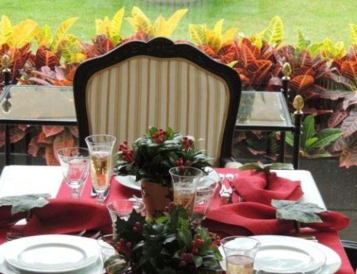 mesa com jogo 6 lugares , com americano vermelho e guardanapos vermelhos, pratos com filetes em tom de ouro. ao centro pequenos vasos com folhagens, junto aos pratos os copos de água e de champanhe.
