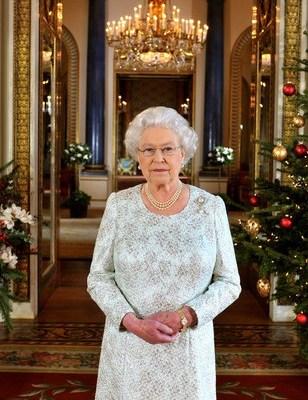 Rainha Elizabeth , usando um vestido azul claro, com as mãos entrelaçadas junto a região do baixo abdomen, parada no corredor do Palácio em Londres, ladeada, a esquerda por um arranjo de natal e a direita por uma árvore de natal , grande, com bolas vermelhas e amarelas .