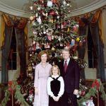 Presidente Jimmy Carter dos Estados Unidos, usando terno escuro ao lado de sua esposa, que usa um vestido lilás clara e a frente sua pequena filha, que usa um vestido preto sem ombros e uma camisa branca, onde logo atrás temos uma enorme árvore de natal com muitos enfeites, tudo isso no salão da Casa Branca, sede do governo americano.