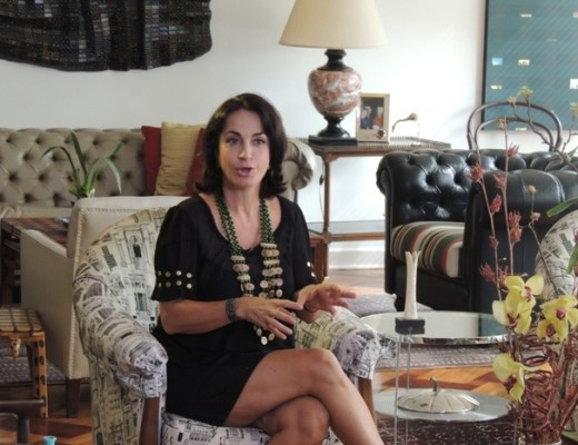 Claudia Matarazzo sentada numa poltrona no centro de numa ampla sala, participa de uma gravação para o Programa Mais Você, da Ana Maria Braga. Ela veste saia e blusa cor preta, um enorme colar com sementes do nordeste. Ela está de pernas cruzadas, olhando para a câmera e gesticula com as mãos.