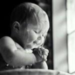 Foto em preto e branco, de uma bebê com 6 meses, recebendo o batismo - a água escorre pela cabeça e ombros nus , enquanto ele aperta as mãos juntas como se estivesse em prece.