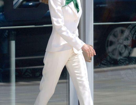 Rainha Letícia da Espanha, em foto de sua chegada a um evento, está andando elegantemente, usando um conjunto de alfaiataria e um lenço verde envolvendo o pescoço.