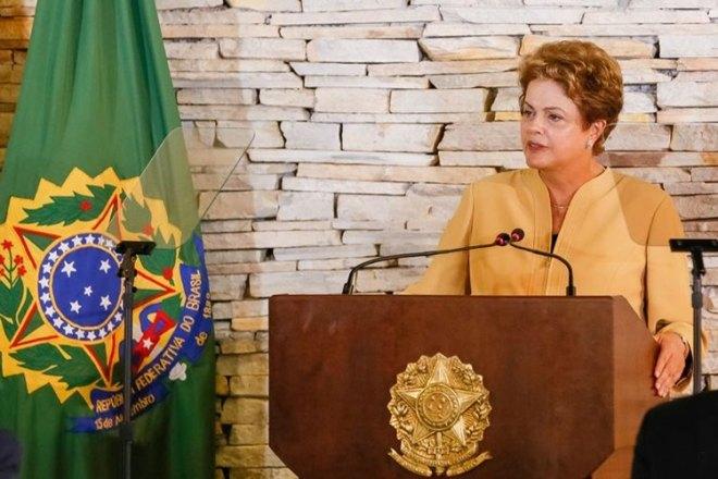 A Presidente Dilma Rousseff está atrás do púlpito presidencial flanco a frente de dois microfones . Atrás dela, a esquerda está a bandeira da República e logo a frente percebe-se um pedestal de girafa com a placa de vidro do teleprompter de onde ela está lendo a fala.