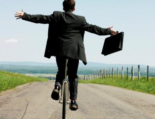 homem de costas, de terno, andando numa bicicleta numa estrada, ela está com os braços aberto, e na mão direita segura uma mala de executivo. Ao fundo um céu azul claro num dia de sol.