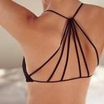 mulher de costas, usando um top preto, onde as alças são fios pretos, semelhante a uma teia de aranha.