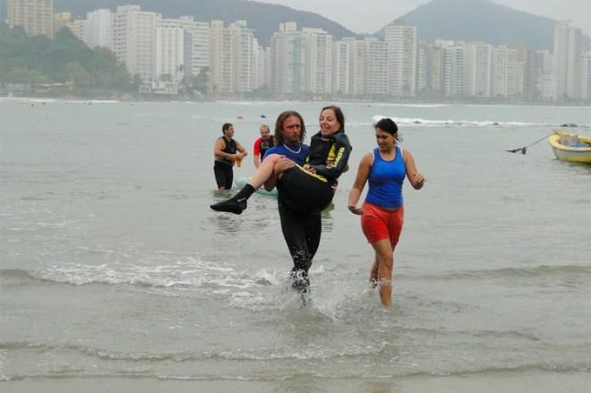 Mara Gabrilli , usando roupas esporte para surf, ela está nos braços de um outro atleta, também vestido com as roupas de mergulho e ao lado um outra jovem caminha, usando com bermuda vermelha e camiseta regata azul.