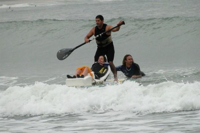 Mara Gabrilli, surfando no mar revolto, com ondas fortes. Ela está posicionada num tipo de cadeira flutuante, ao seu lado um surfista, nada ao seu lado e outro surfista logo atrás de pé com um remo nas mãos.