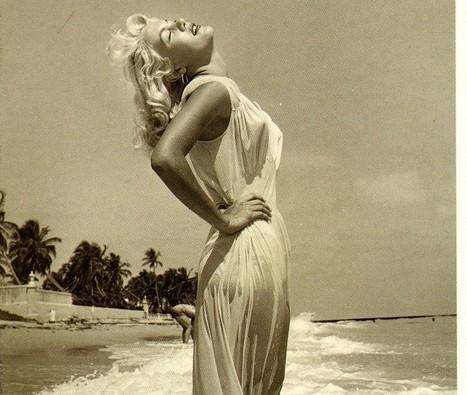 Atriz Marilyn Monroe, loira, na praia, junto as marolas ,usando uma saida de praia transparente,