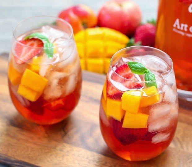 bandeja de madeira, com 2 copos estilo drink, com chá gelado, decorados com vários tipos de frutas cortadas em cubos, rodelas de limão e folhas de hortelã nas bordas