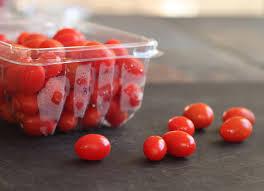 pote plástico com tomates cerejas e alguns estão soltos sobre a bancada.