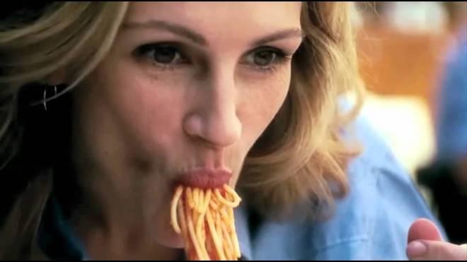 atriz Julia Roberts comendo macarrão numa cena de um filme. Ela tenta engolir uma grande quantidade de macarrão.