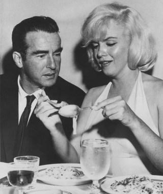 Atriz Marilyn Monroe, numa mesa de jantar, tenta comer macarrão usando garfo e colher, ao seu lado um homem de terno escuro está olhando para o gesto dela. Na mesa além dos pratos , tem uma taça com água e outra com vinho tinto. Ela usa um vestido claro, preso no pescoço e sem mangas.