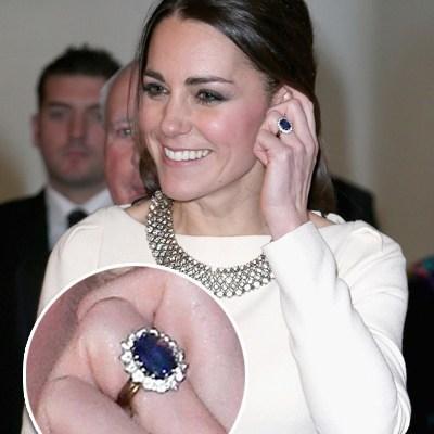Princesa Kate Middleton, usando um lindo vestido na cor branca, tem sua mão junto ao rosto, onde mostra seu lindo anel de noivado, em safira azul.