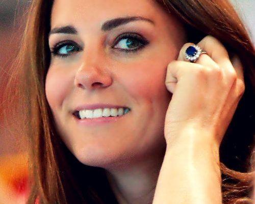 Princesa Kate Middleton, do Reino Unido, casada com Príncipe William, está sorrindo e tem a sua mão esquerda junto ao rosto mostrando seu lindo anel,