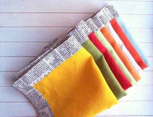 guardanapos de tecido de várias cores, sendo amarelo o que está logo acima, eles estão sobre uma mesa de madeira.