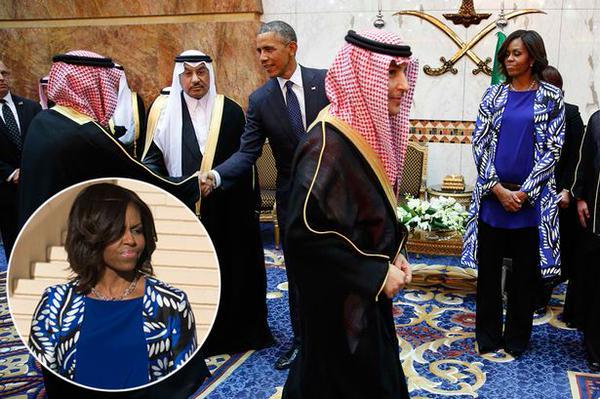 """O Presidente Barack Obama, dos Estados Unidos da América, cumprimenta uma autoridade da Arabia Saudita, observado por outro dignatário árabe. Ambos os árabes usam o """"fez""""(adereço de cabeça típico) . Em segundo plano Michelle Obama, vestindo uma pantalona preta e uma túnica estampada, com folhas brancas sobre o azul royal observa a cena. Ela está com os cabelos na altura do ombro e sua cabeça está descoberta - o que não é ideal para uma encontro protocolar como esse."""