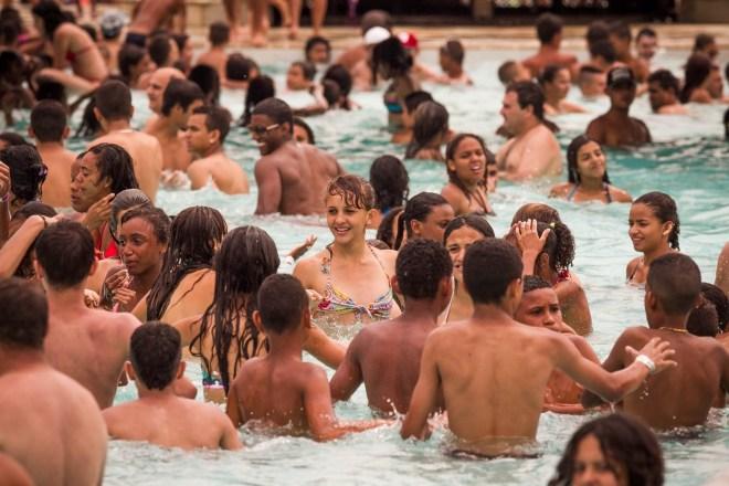 Numa piscina popular lotada com jovens e crianças brincam.