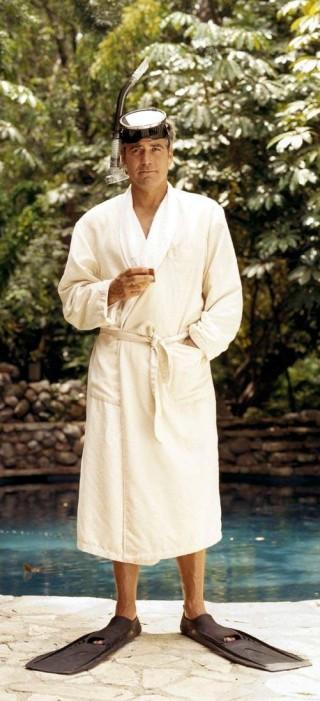 O ator George Clooney, junto a uma piscina, veste um roupão , na cor branca, usa óculos de mergulho na testa e um pé de pato, para mergulho.