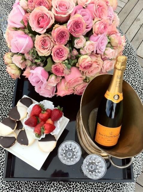 Numa mesa, de jardim, uma bandeja em madeira, cor preta, sobre ela um buquê de rosas , na cor rosa clara, junto as elas um prato com morangos, e ao lado um balde com uma garrafa de champanhe Veuve Clicquot fechada, junta ao balde duas taças de cristal vazias.