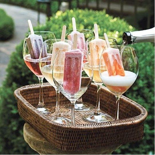 Num jardim, bandeja artesanal, com seis taças de cristal, dentro delas sorvetes coloridos, e está sendo servido champanhe nas taças.