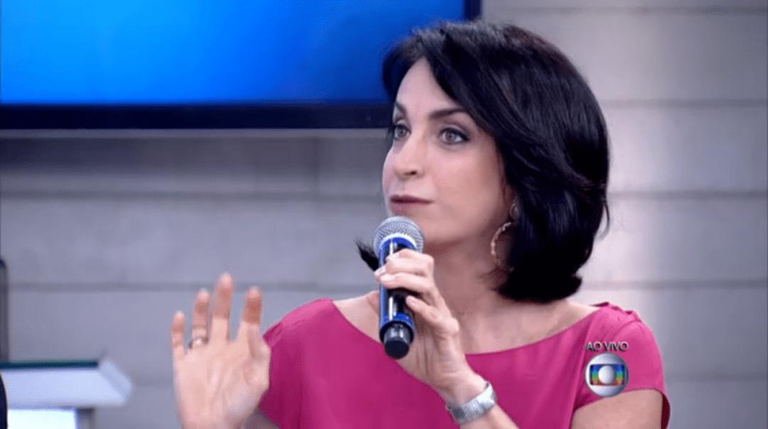Claudia Matarazzo, durante o programa Encontro com Fatima Bernardes da Rede Globo, ela está usando um vestido rosa, num close fechado, ela olha para a apresentadora, e segura um microfone com a mão esquerda. No seu pulso um relógio com pulseira prateada.