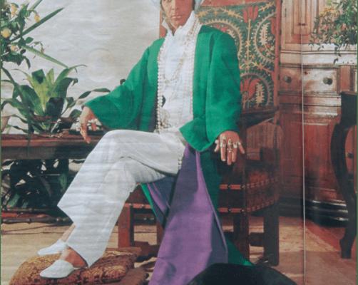 O estilista Dener, numa sala usa uma roupa branca e uma capa verde com calda muito grande. Deitado na calda um cachorro preto com coleira. Dener usa um turbante com pedra e penugem verde.