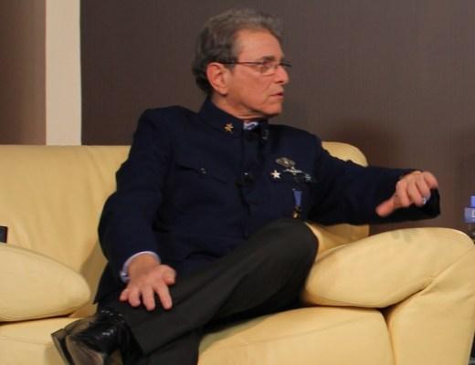 O estilista José Gayegos, de cabelos grisalhos cotados rentes a cabeça, está sentado em um sofá de cor creme vestindo um paletó marinho tipo farda. Na lapela e junto ao ombro usa 4 condecorações