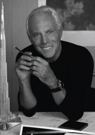 Giorgio Armani, estilista, está na sua mesa de trabalho, usa blusa preta, está com os cotovelos sobre a mesa e segura na mão direita um lápis, sobre a mesa muitos papéis. Ele mantém o seus cabelos grisalhos.