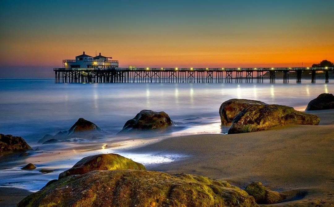 Imagem da praia de Malibu, Califórnia , Estados Unidos, numa vista da praia para o mar. Ao fundo temos uma passarela suspensa, feita em madeira, e ao final um amplo ambiente, como fôsse um mirante, ele é madeira pintada de branco.