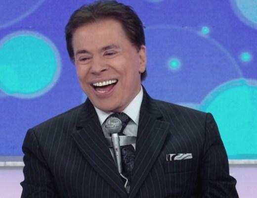 O Apresentador Silvio Santos, numa cena do ,seu programa de TV, ele está sorrindo, com cabelos escuros. Ele veste um terno escuro , camisa branca, gravata escura com detalhes em tons escuros e o famoso microfone sobre a gravata