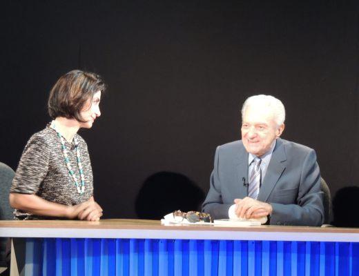 Claudia Matarazzo, vestindo uma blusa em tons de cinza, está numa bancada junto ao jornalista Salomão Schatvazman durante uma entrevista para a TV Band News, ele veste terno cinza claro, camisa cinza clara e gravata na cor cinza com listras cinzas mais escuras.