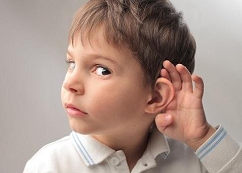 menino olhando de lado e olhos numa visão lateral, está com a mão esquerda aberta junto a orelha esquerda, como estivesse tentando escutar melhor.