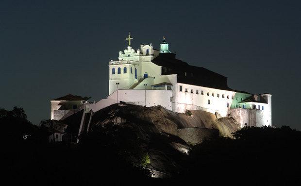 Igreja e Convento de Nossa Senhora da Penha, em Vila Velha, Espirito Santo. Na imagem noturna, aparece toda a construção, na cor branca no topo de um monte sobre as pedras e apenas uma escada de muitos degraus.