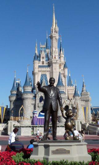 Foto da Disneylandia com os castelos ao fundo e a frente a estátua em bronze do Walt Disney e o Mickey.