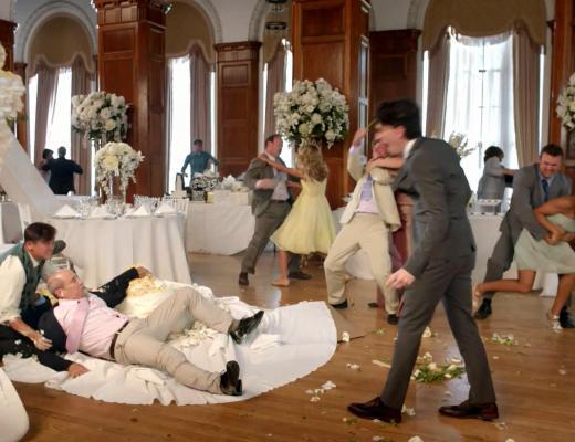 Festa de casamento, num amplo salão, onde seis casais brigam junto as mesas e um homem está caído sobre uma mesa quebrada e outro homem grita e gesticula para com ele. Todos usam ternos e as mulheres usam vestidos cada um de cor diferente.