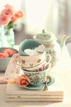 a foto mostra quatro delicadas xícaras de chá, empilhadas. a primeira, verde agua com desenhos de flores em azul e verde. a segunda e terceira são brancas com flores pequenas e delicadas rosas e a ultima verde agua. Ao fundo, vemos um bule de chá em porcelana verde com detalhes em dourado e pequenas flores rosas. Na imagem também, um vasinho de flor verde com rosas cor de rosa.