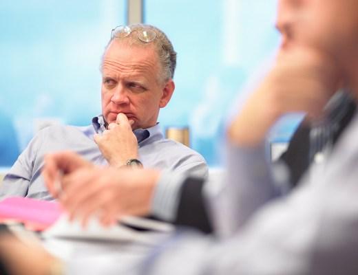 Numa reunião empresarial, homem com cabelos grisalhos, usando apenas camisa Social, está atento e outros pessoas participam dessa reunião.