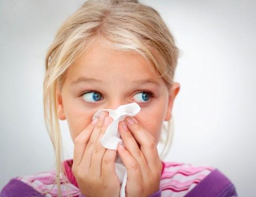 Menina loirinha de olhos muito azuis, com cerca de 6 anos, assoa o nariz com expressão angustiada