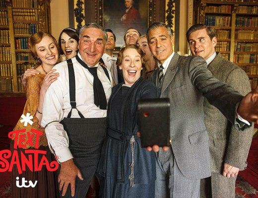 """George Clooney esteve nos estúdios de gravação do seriado """"Downton Abbey"""" e fez uma selfie junto aos atores . Eles estão sorrindo e uma atriz segura o smartphone."""