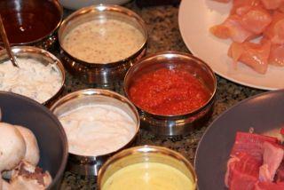 a foto mostra varios potinhos de inox com molhos. Mostarda, molho de iogurte, molho rose. Ao lado, dois potes com frango e carne.
