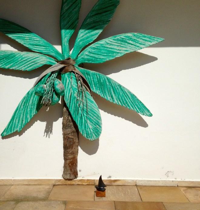 Escultura de Palmeira em madeira colocada junto a parede externa de casa em tamanho natural com o tronco marrom e as folhas verdes
