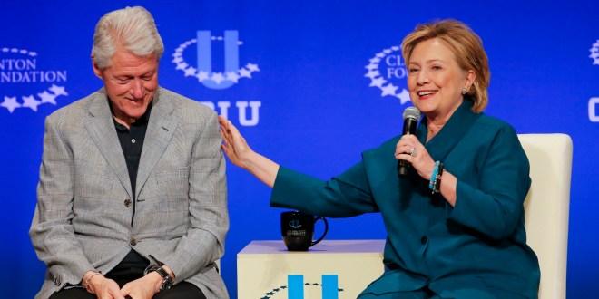 Bill Clinton ao lado de Hillary Clinton, durante uma entrevista na Fundação Bill Clinton, ambos estão sentados, ela está a esquerda dele. Ele veste uma camisa azul escura e blazer cinza claro. Ela está vestindo um conjunto azul petróleo e está com o microfone na mão esquerda.