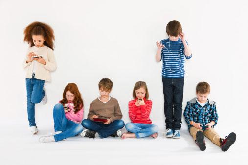 a foto mostra 6 crianças entre 8 e 10 anos com celular. duas estão em pé e as outras sentadas. Estão lado a lado e cada uma está com seu celular, algumas digitando e outras ouvindo música